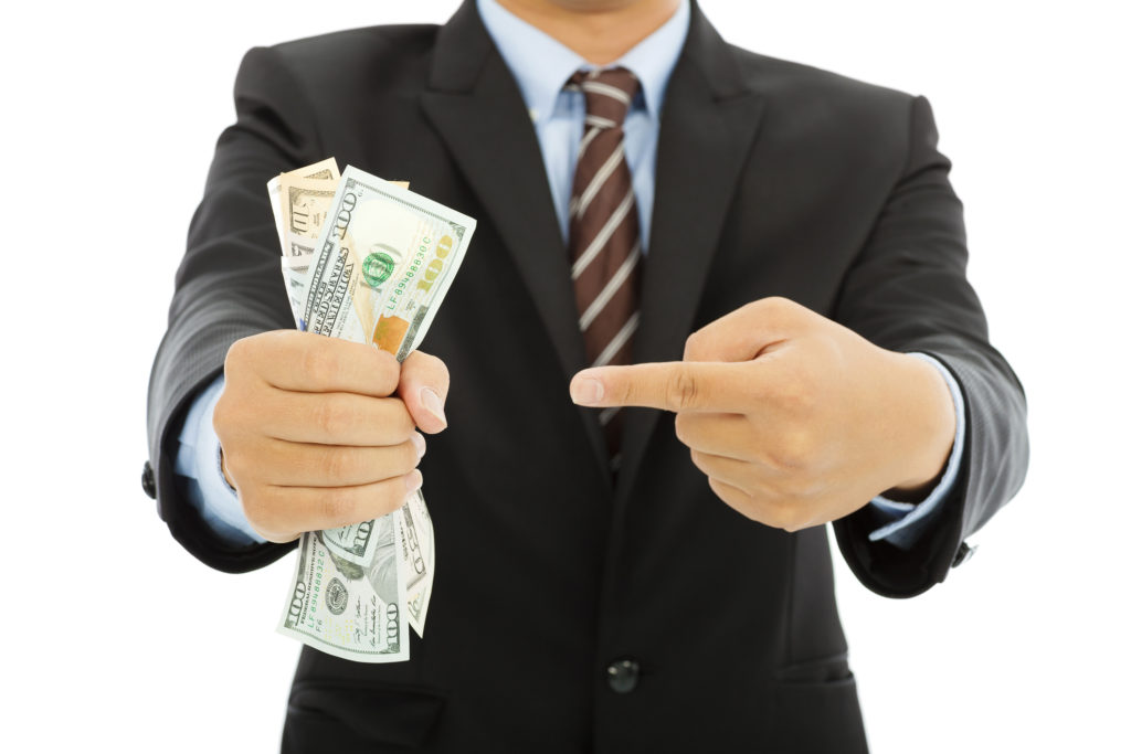 Man in suit holding a fistful of cash