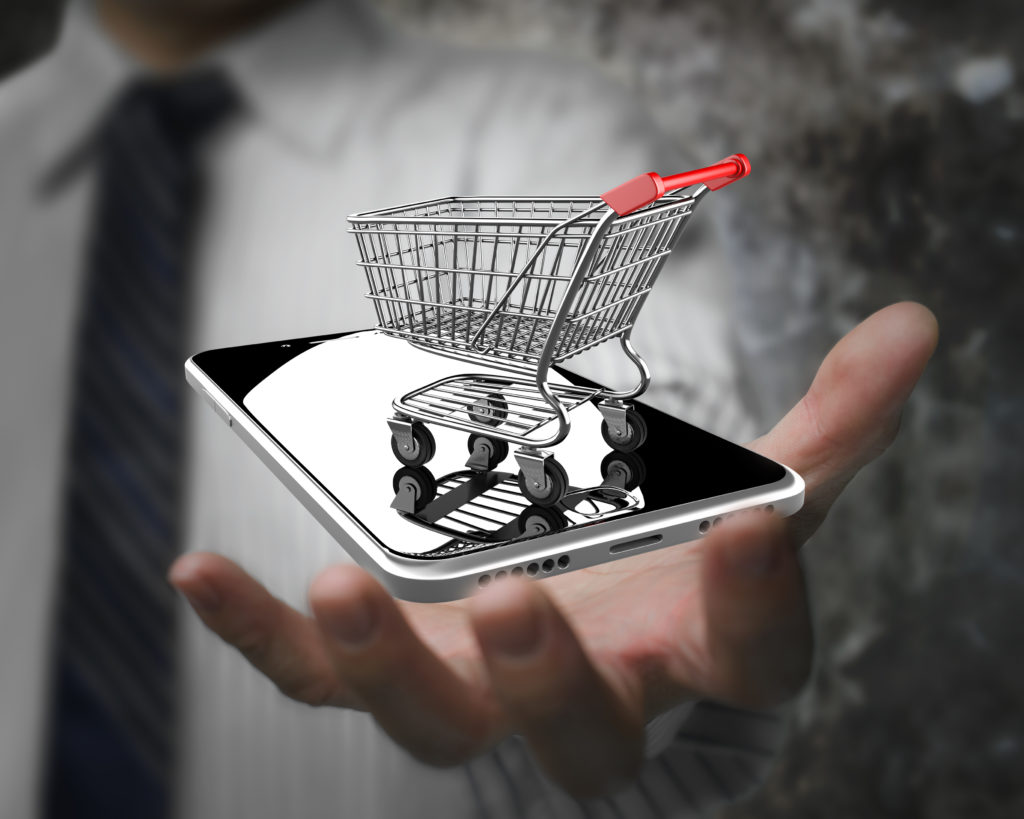Businessman hand showing shopping cart with smart phone, online shopping concept.