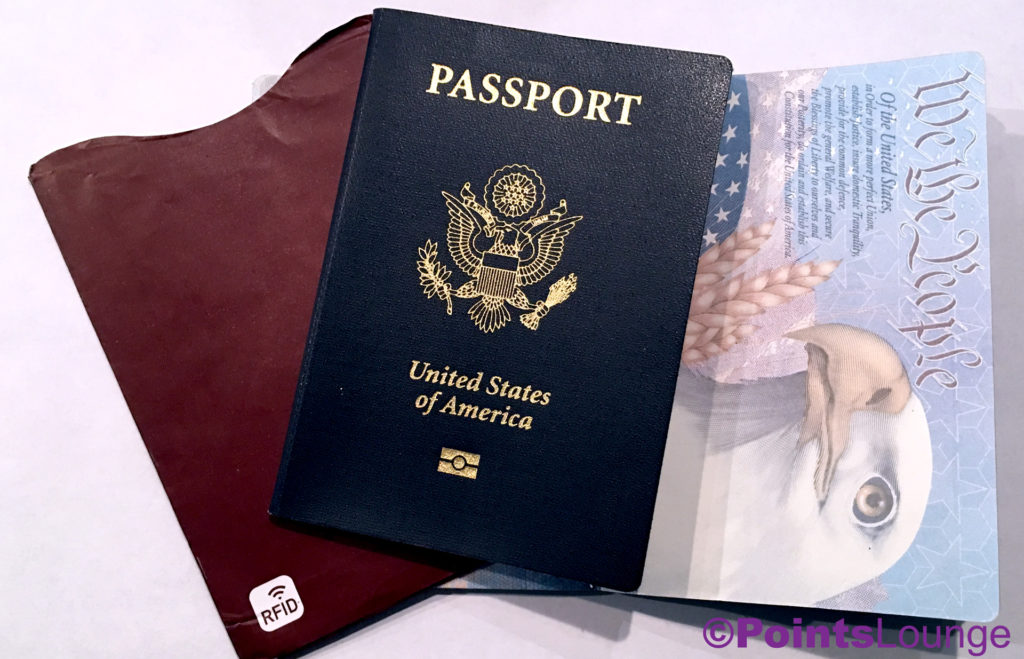 """United States Passport, RFID protection sleeve, and USA passport opened to """"We the People"""" page."""