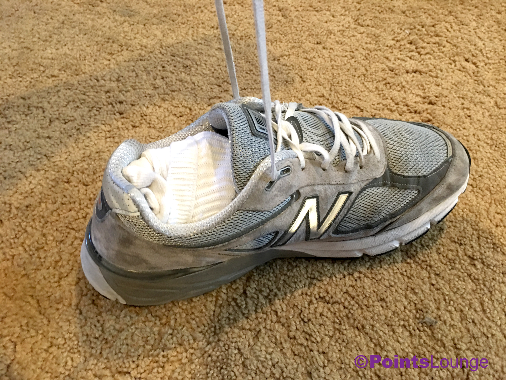 Tightening a New Balance M990GL4 Grey/Castlerock shoe packed with socks.