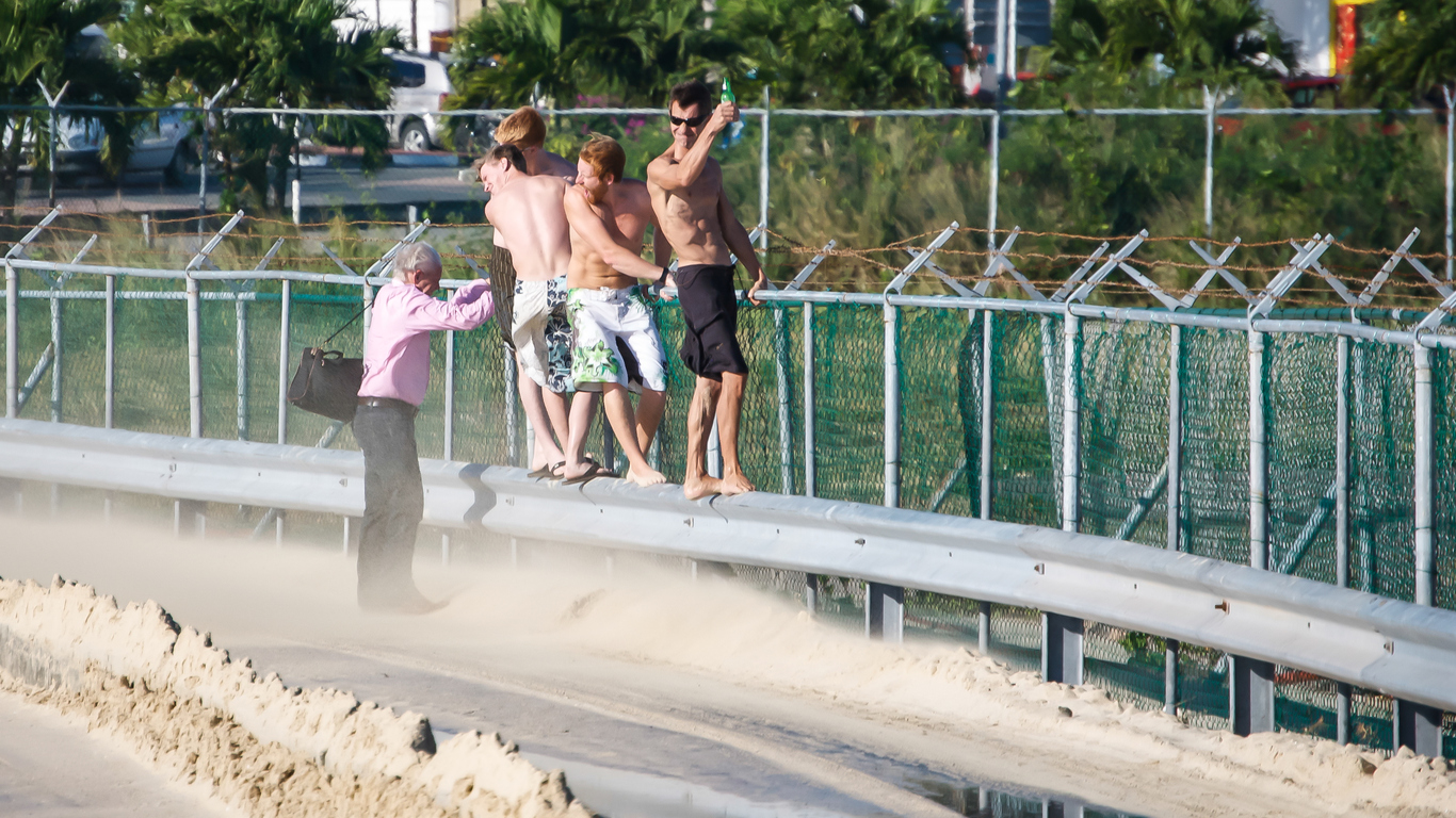 Maho Beach, St. Maarten-December 28, 2009: a group of thrill seeking beach goers hold on tightly to the fence while being blasted by a jet's exhaust at the runway on St. Maarten.