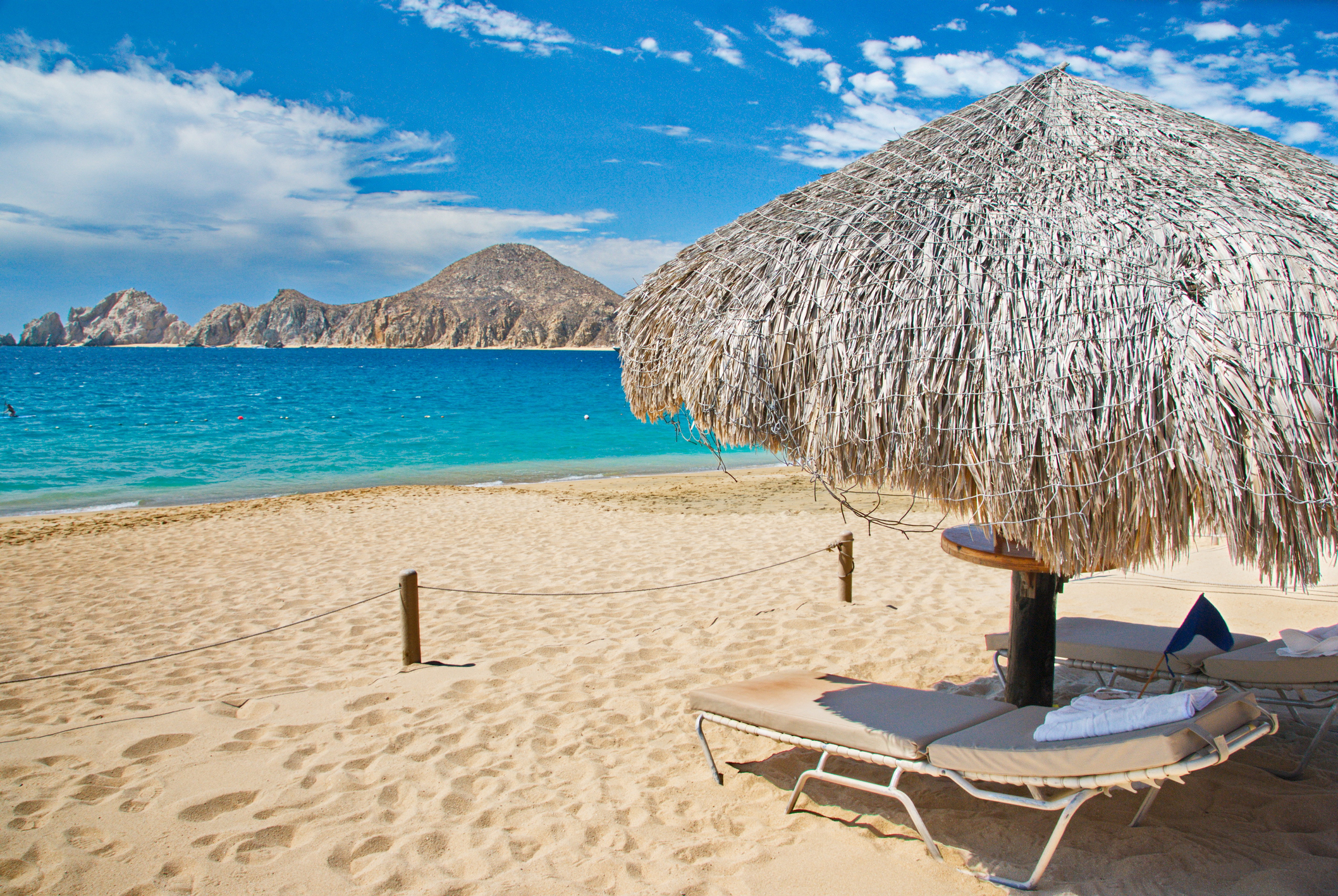 Beach location with chaise and umbrella for relaxation in Cabo San Lucas, Mexico with mountains in view across the water. (Photo: ©iStockphoto.com/JulieHewitt)