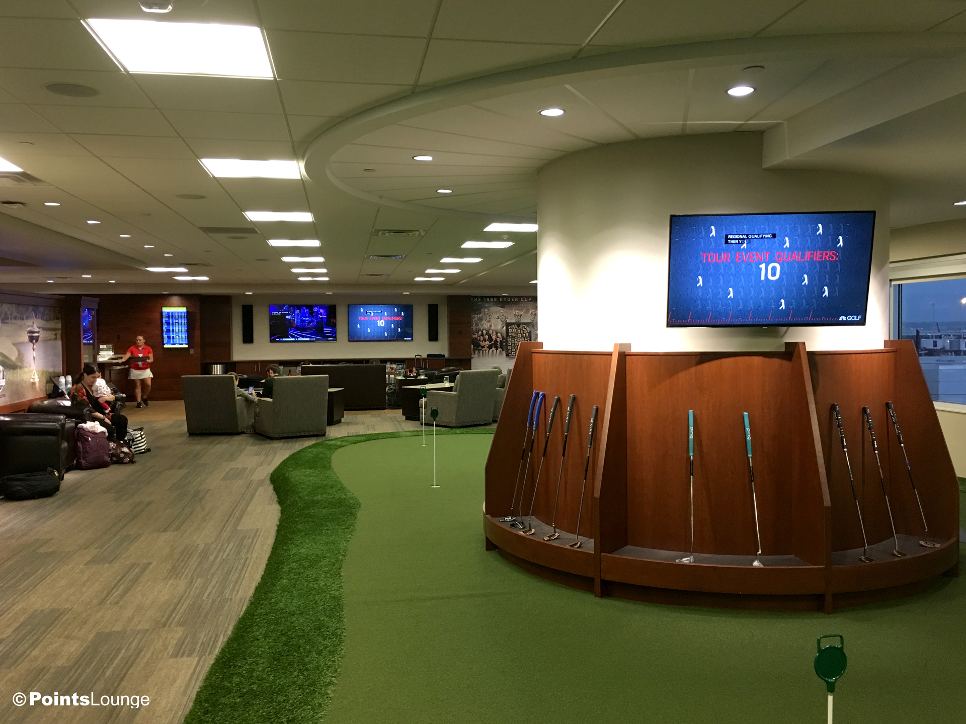 A putting green and putters are seen inside PGA MSP golf-themed airport lounge at the Minneapolis-St. Paul International Airport. One of the ways the lounge can be accessed is with Priority Pass membership. (Click for a larger image.)