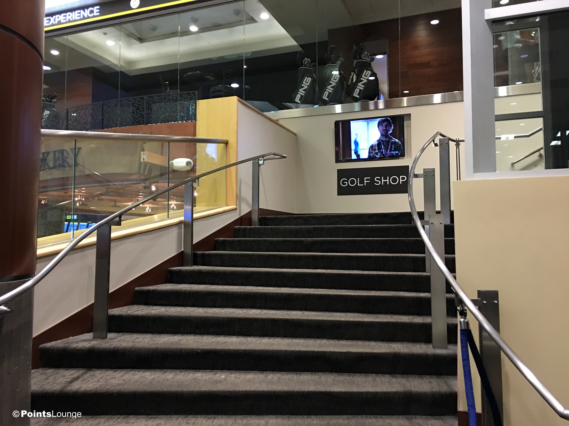 A view of the entrance stairs outside the PGA MSP golf-themed airport lounge, as seen from the main course atrium at Minneapolis-St. Paul International Airport. One of the ways the lounge can be access is with Priority Pass membership. (Click for a larger image.)