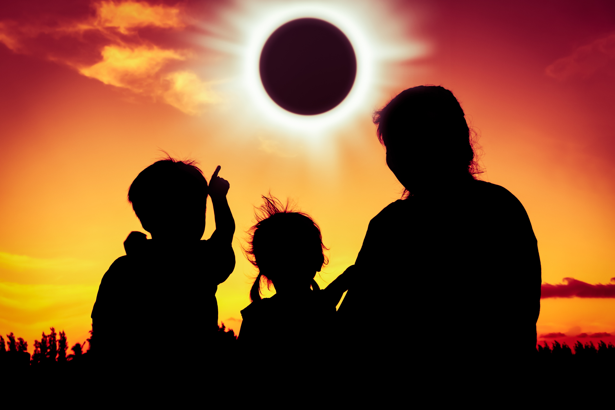 View of a family watching total solar eclipse. Natural phenomenon. Silhouette back view of family sitting and relaxing together. Boy point to solar eclipse on gold sky background. Happy family spending time together. Outdoor. (Photo: ©iStockphoto.com/kdshutterman)